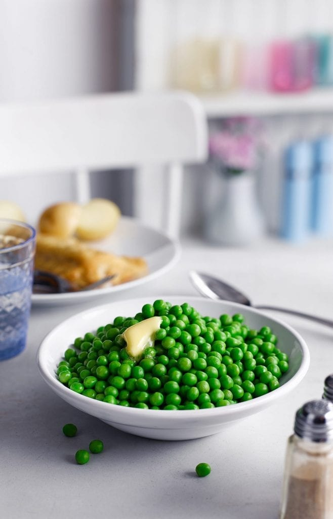 Cooked frozen peas with butter melted over the top. A meal with drinks in the background. Shot for Birds Eye.
