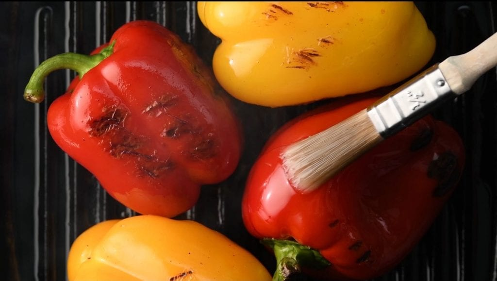 Showreel displaying roasted peppers being brushed with oil, roasted tomatoes being turned on the griddle and salt being added to roasted aubergine.