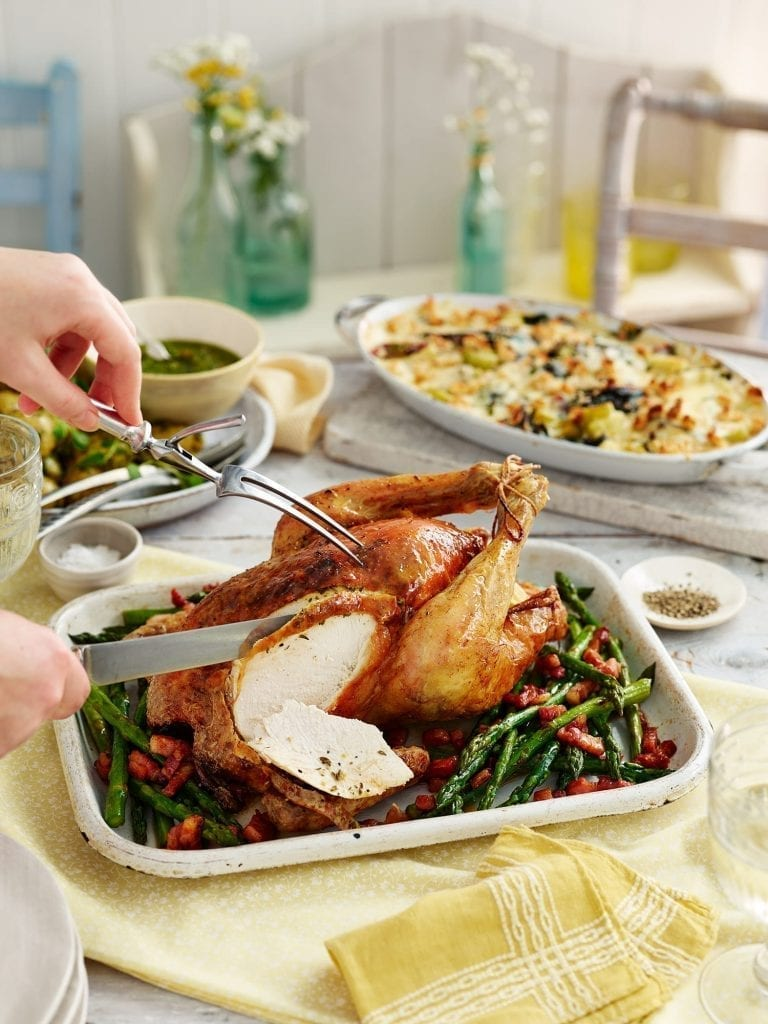 Thyme Buttered Roast Chicken being carved. Served with green beans. Shot for Good Housekeeping for a Bank Holiday menu feature.