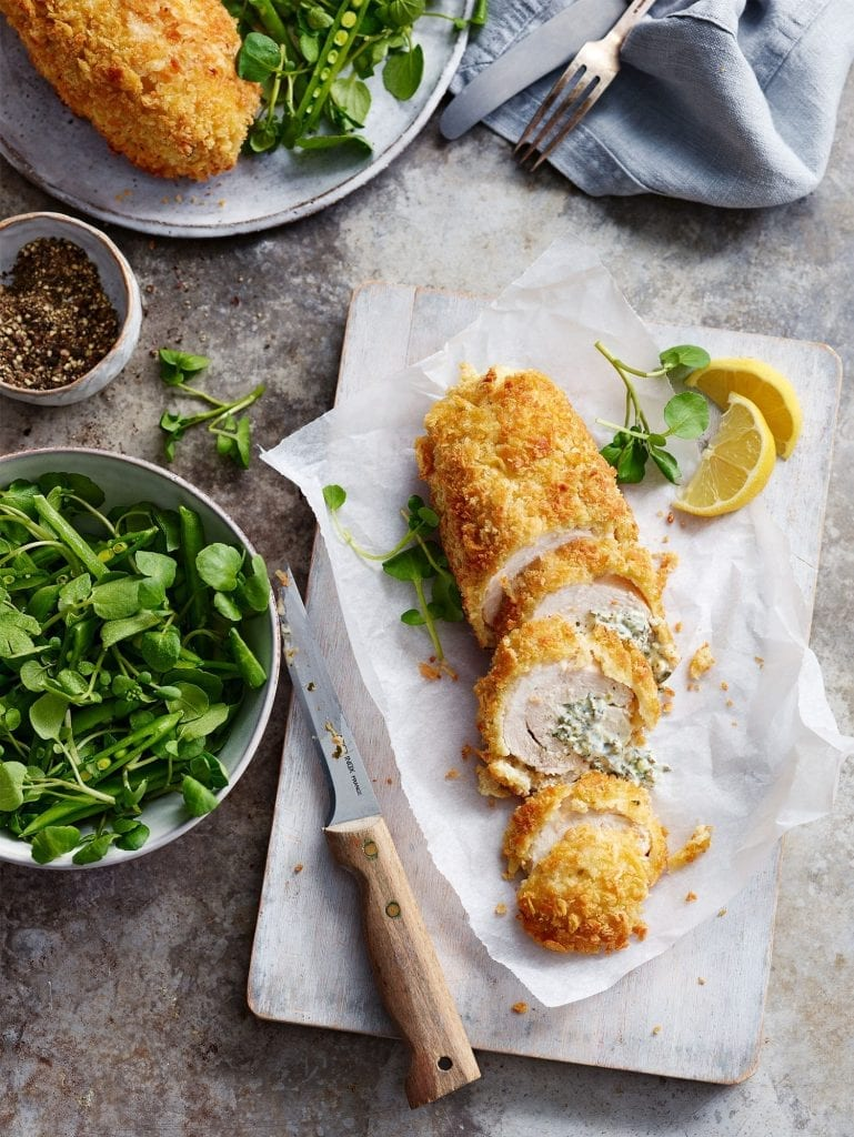 Chicken Kiev Watercress salad Sliced chicken breadcrumbs overhead lemons